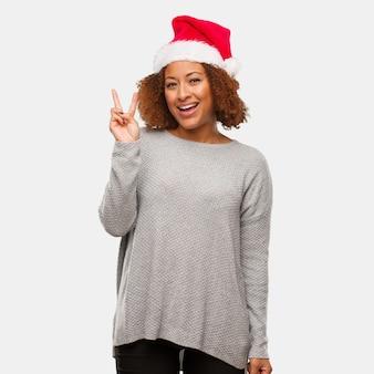 Jovem mulher negra vestindo um chapéu de papai noel divertido e feliz fazendo um gesto de vitória