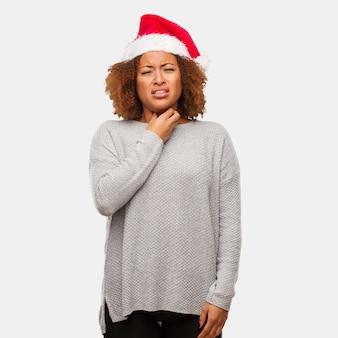 Jovem mulher negra vestindo um chapéu de papai noel, tosse, doente devido a um vírus ou infecção