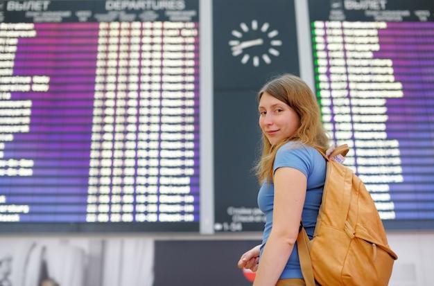 Jovem mulher no aeroporto internacional, com placa de vôo