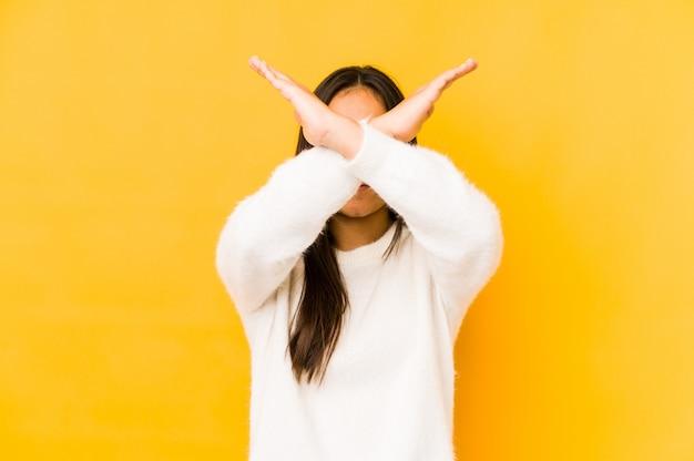 Jovem mulher no amarelo que mantém dois braços cruzados, conceito da negação.