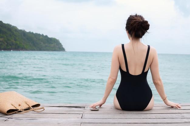 Jovem mulher no banho de sol do roupa de banho na praia do cais no mar, conceito das férias de verão.