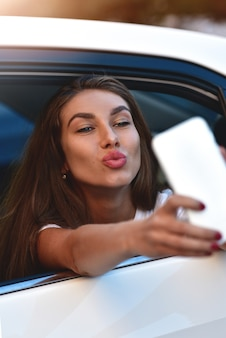 Jovem mulher no carro vai de férias como passageira faz selfie.