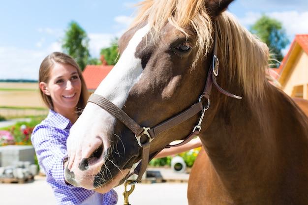 Jovem mulher no estábulo com cavalo e é feliz