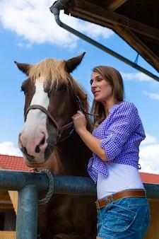 Jovem mulher no estábulo com cavalo na luz do sol
