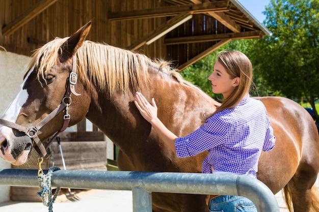 Jovem mulher no estábulo com cavalo