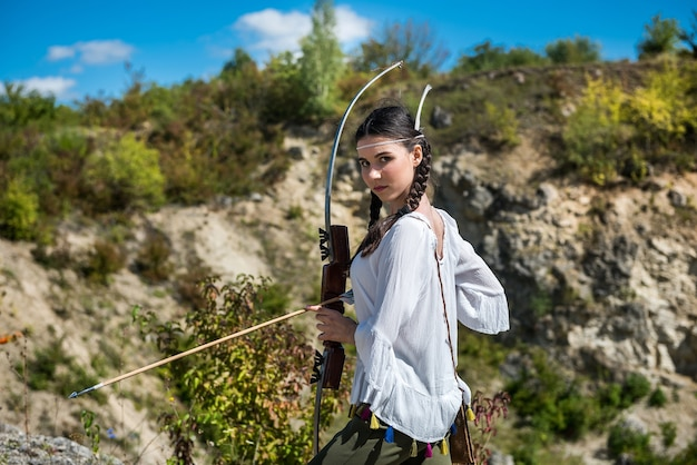 Jovem mulher no estilo dos povos nativos da américa com um arco e flecha na natureza