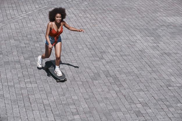 Jovem mulher no estilo livre andando de skate na rua Foto Premium