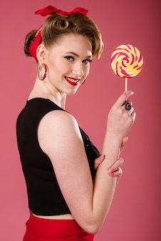 Jovem mulher no estilo retrô, posando com um doce pirulito no fundo rosa. retrato de pin-up