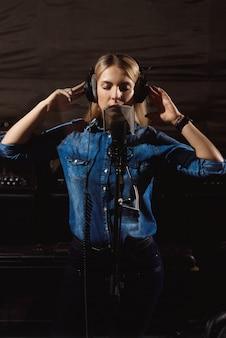 Jovem mulher no estúdio de gravação falando no microfone.