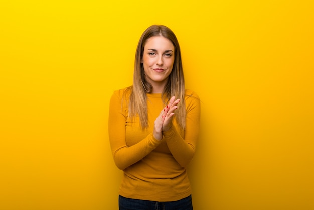 Jovem mulher no fundo amarelo aplaudindo após apresentação em uma conferência