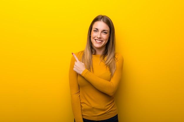 Jovem mulher no fundo amarelo apontando para o lado para apresentar um produto