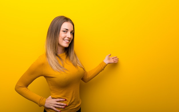 Jovem mulher no fundo amarelo apontando para trás e apresentando um produto