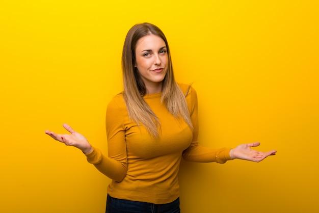 Jovem mulher no fundo amarelo infeliz e frustrado com alguma coisa porque não entender algo