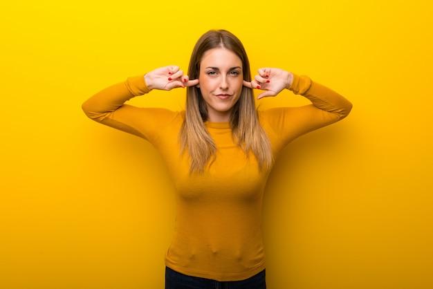 Jovem mulher no fundo amarelo que cobre ambas as orelhas com as mãos