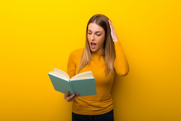 Jovem mulher no fundo amarelo surpreendeu ao apreciar a leitura de um livro