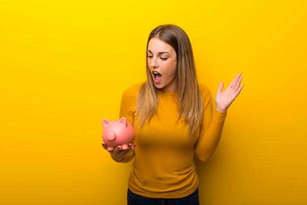 Jovem mulher no fundo amarelo surpreendeu ao prender um piggybank