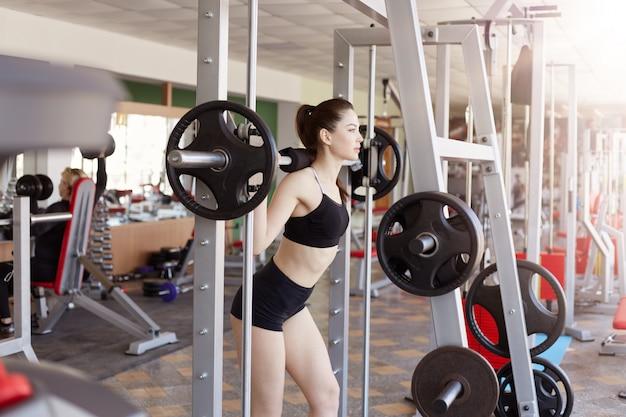 Jovem mulher no ginásio fazendo agachamentos com peso extra nos ombros, bela mulher malhando no health club, mulher desenvolver definição dos músculos, desenvolvendo a definição dos músculos.