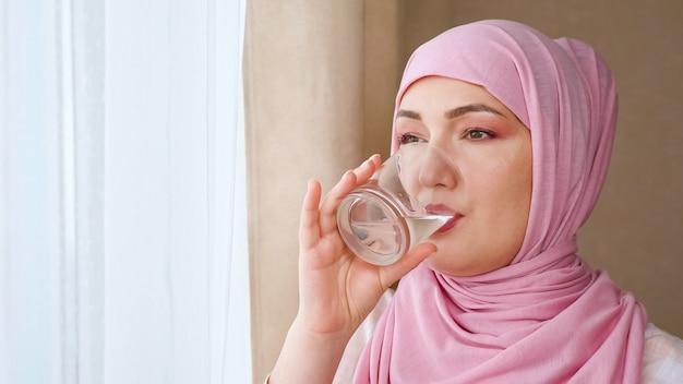 Jovem mulher no hijab bebe água de um copo.