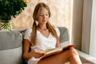 Jovem mulher no livro de leitura de t-shirt branca no sofá em casa