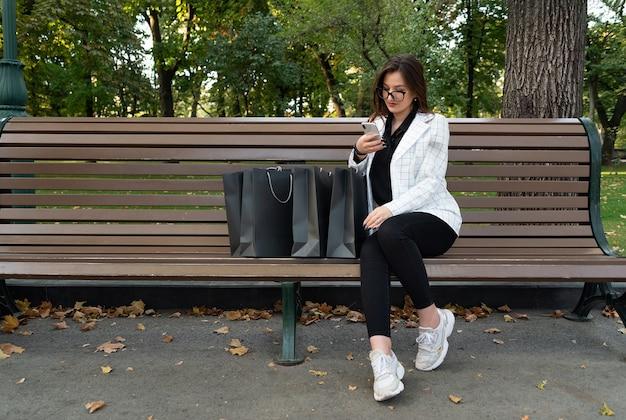 Jovem mulher no parque com sacolas de compras e telefone. compras online. descontos, promoções, black friday.