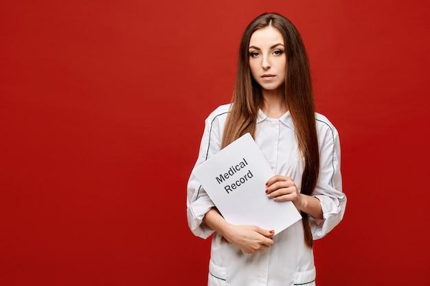 Jovem mulher no revestimento médico branco que guarda um informe médico em suas mãos, espaço da cópia, isolado. conceito de saúde