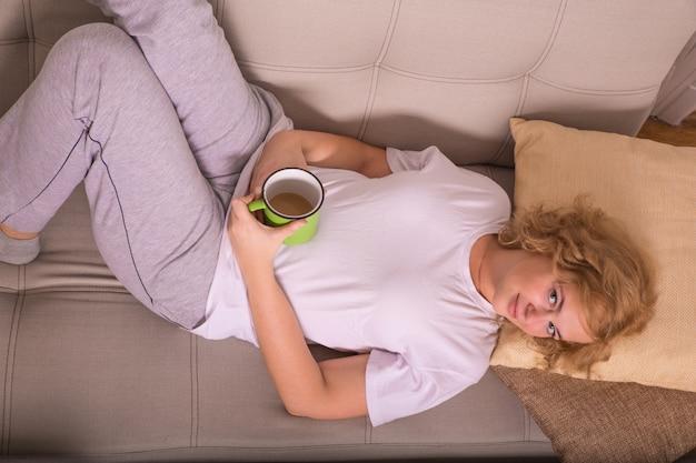 Jovem mulher no sofá no início da manhã