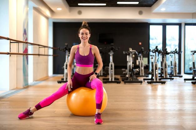 Jovem mulher no sportwear esporte exercício sagacidade fitball amarelo no ginásio
