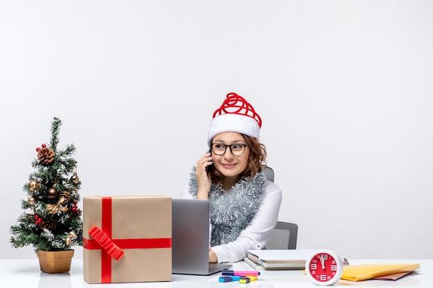 Jovem mulher no trabalho durante as férias usando laptop em fundo branco.