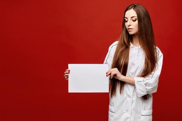 Jovem mulher no uniforme médico que levanta com uma folha de papel branca vazia no fundo vermelho, isolado, copie o espaço para seu texto. conceito de saúde
