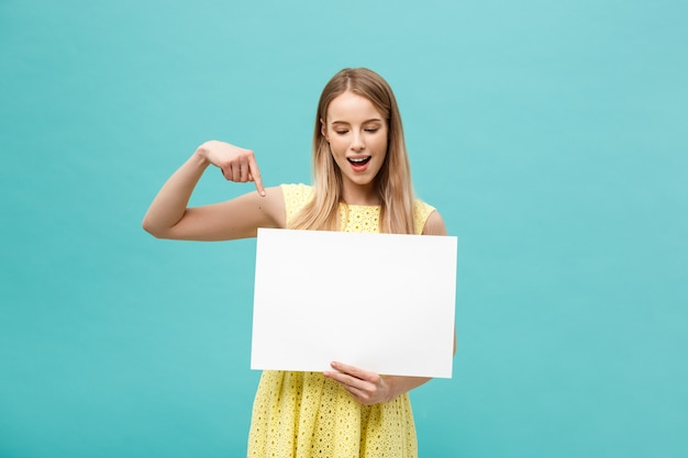 Jovem mulher no vestido amarelo, apontando o dedo para o quadro branco em branco do lado. isolado sobre azul