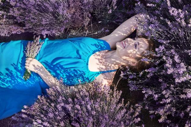 Jovem mulher no vestido azul romântico relaxar em campos de lavanda. garota romântica encontra-se em flores de lavanda e sonhos