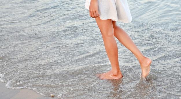 Jovem mulher no vestido branco que anda apenas na praia.