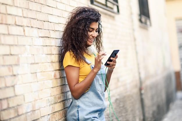 Jovem mulher norte-africana que texting com seu telefone inteligente ao ar livre