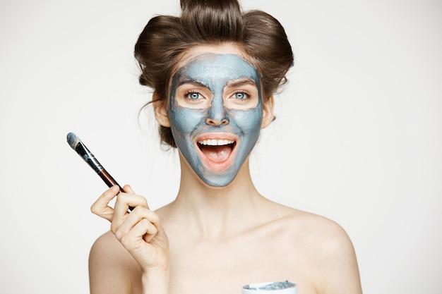 Jovem mulher nua bonita em rolos de cabelo, cobrindo o rosto com mack. tratamento facial. cosmetologia de beleza e spa.