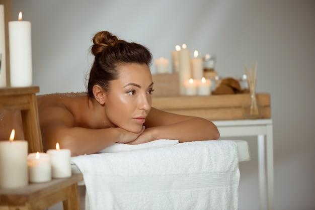 Jovem mulher nua relaxante no salão spa.