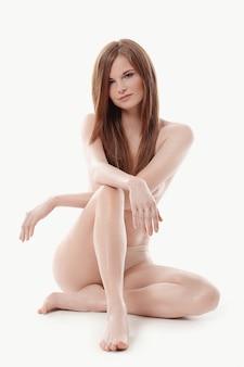 Jovem mulher nua sentada no chão, corpo e conceito de cuidados com a pele