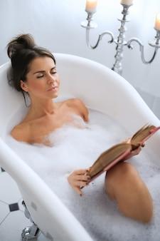 Jovem mulher nua tomando um banho de espuma relaxante e lendo um livro