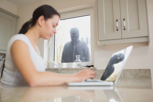 Jovem mulher observada na cozinha