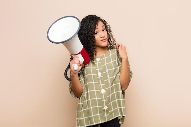 Jovem mulher olhando arrogante, bem sucedido, positivo e orgulhoso, apontando para si mesmo segurando um megafone