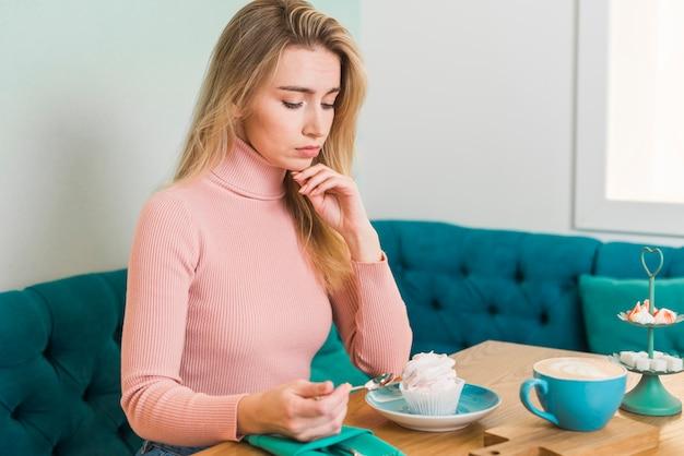 Jovem mulher olhando merengue no café