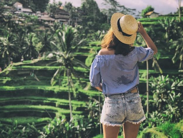 Jovem mulher olhando o lindo terraço de arroz tegallalang em bali