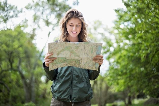 Jovem mulher olhando o mapa em pé na floresta