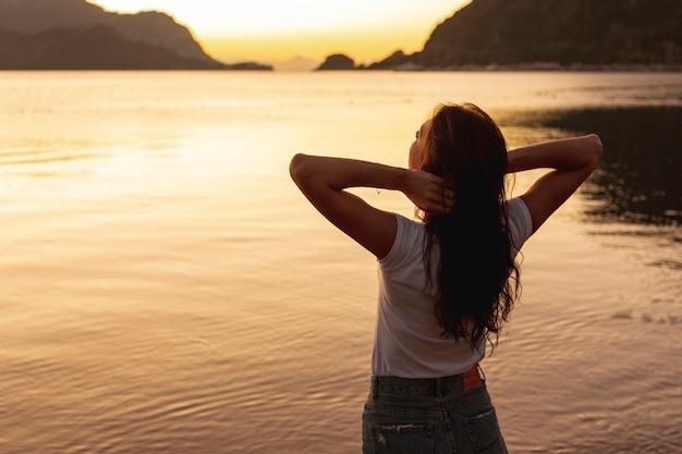 Jovem mulher olhando o pôr do sol na margem de um lago