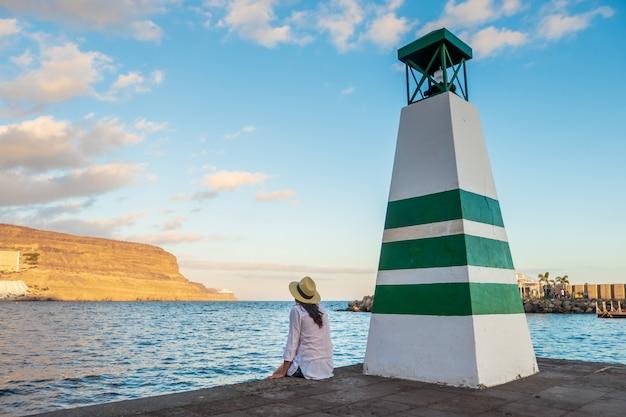 Jovem mulher olhando para o mar pelo farol