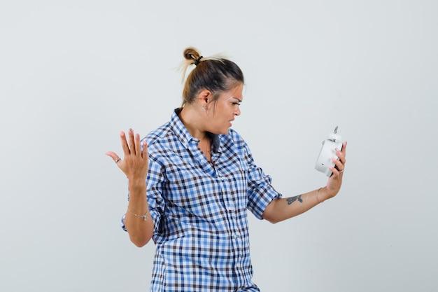 Jovem mulher olhando para o relógio enquanto levanta a mão com maneira agressiva de camisa quadriculada e parece nervosa.