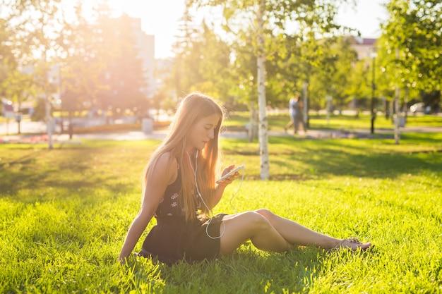 Jovem mulher olhando para smartphone e ouvindo música no parque.
