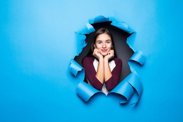 Jovem mulher olhando pelo buraco azul na parede de papel.