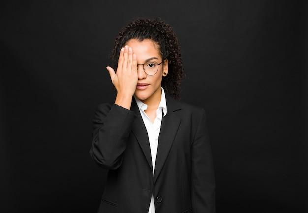 Jovem mulher olhando sonolenta, entediada e bocejando, com dor de cabeça e uma mão cobrindo metade do rosto sobre a parede preta