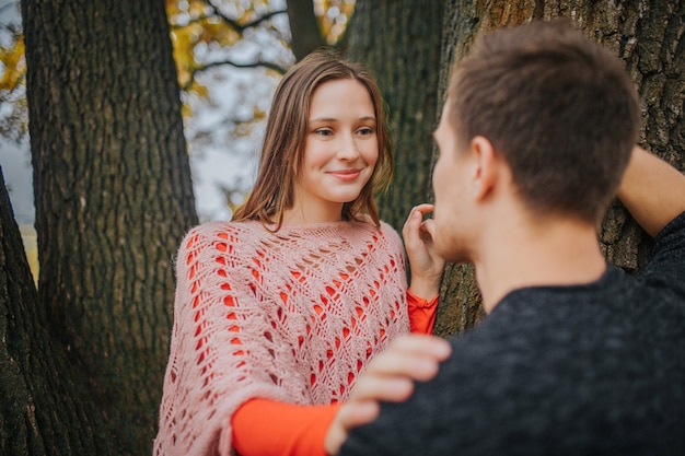 Jovem mulher olhar para o homem e sorrir. ela está apaixonada. mulher toca nele. ele se apoia na madeira.