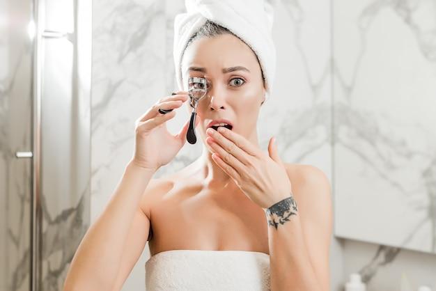 Jovem mulher ondulando cílios com um encrespador envolto em toalhas no banheiro